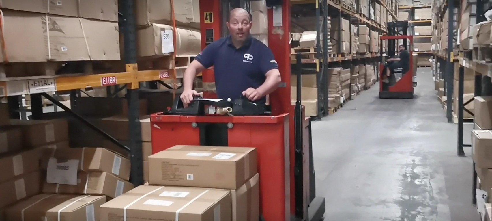 Man in warehouse distribution centre on a forklift truck